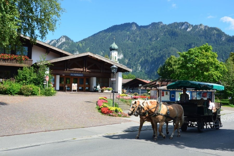 A carriage, pulled by two light-brown horses, drives in front of Oberammergau's Tourist Office and the Ammergauer Haus.