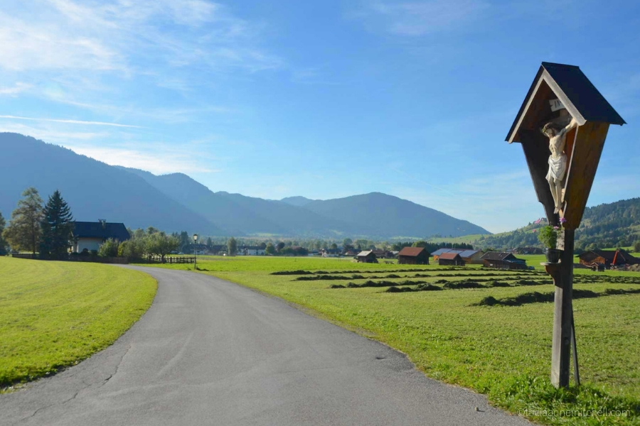 A paved road surrounding by mountains and agricultural fields in the German town of Oberammergau.