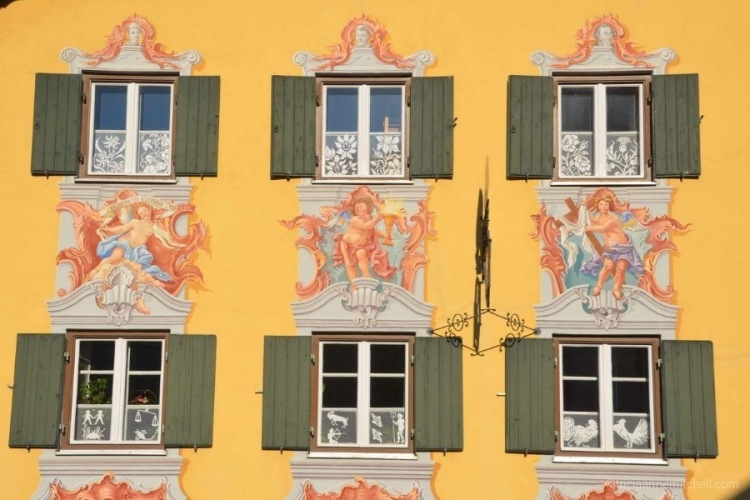A close-up of a traditional Bavarian home: The wall is painted yellow, there are 6 green shutters, and murals of angels.