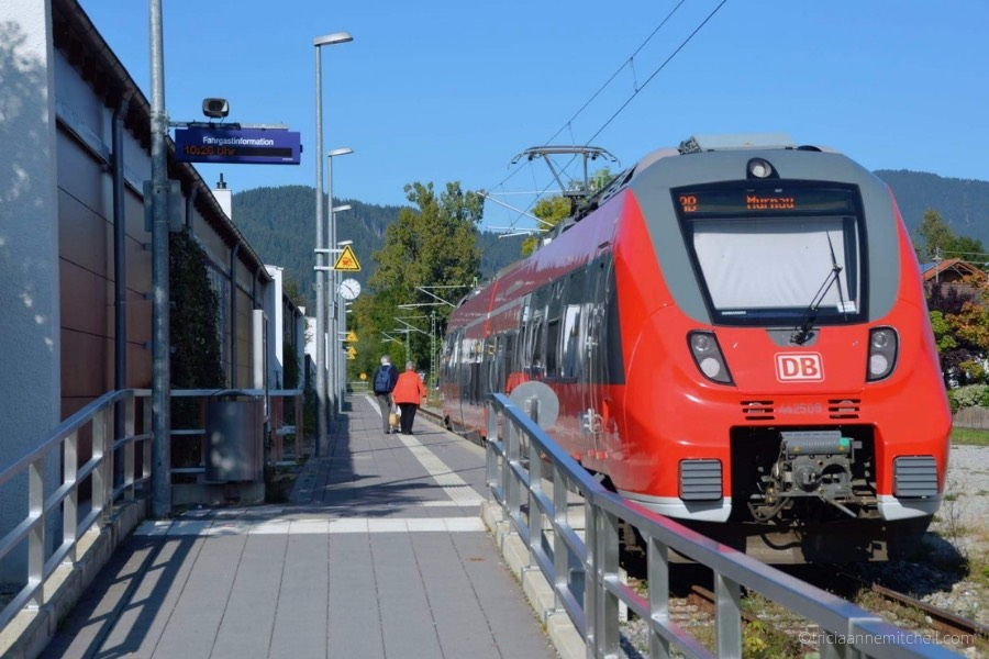 A red German train sits at the train stop in Oberammergau, Germany. The letters