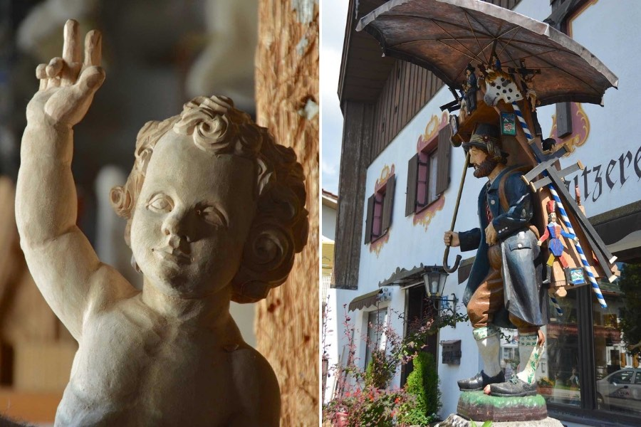 Woodcarvings on display in Oberammergau. One features an angel or cherub with its hand outstretched. It is unpainted. The other is on display outside a woodcarver's shop. It is painted and depicts a traveling merchant from centuries ago. He has wooden items for sale in a rack that he is wearing on his back. He is wearing traditional clothes and is carrying an umbrella.