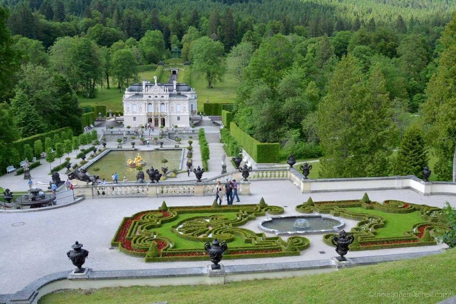 An overhead view of Linderhof Palace's terraced gardens and fountains. The hills surrounding the castle are covered in green trees.