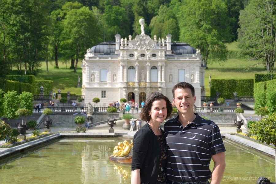 The Linderhof Palace Gardens on a sunny day: The bushes and trees are green, and there is a fountain in front of the white palace building.