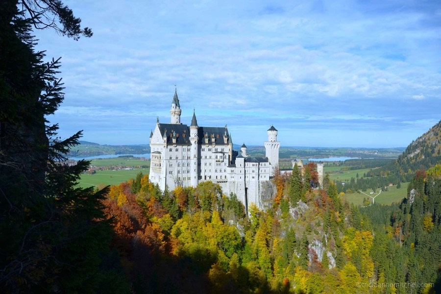 Germany's Neuschwanstein Castle, surrounded by red, green, and yellow foliage, on a sunny day.