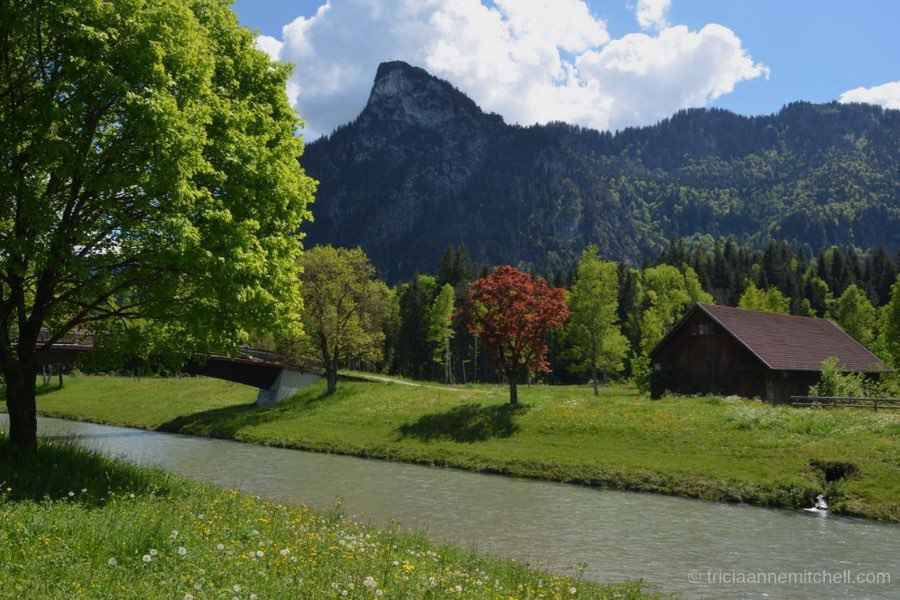 The Kofel, a cone-shaped mountain towers over a river and wooden barn. Green trees are visible.