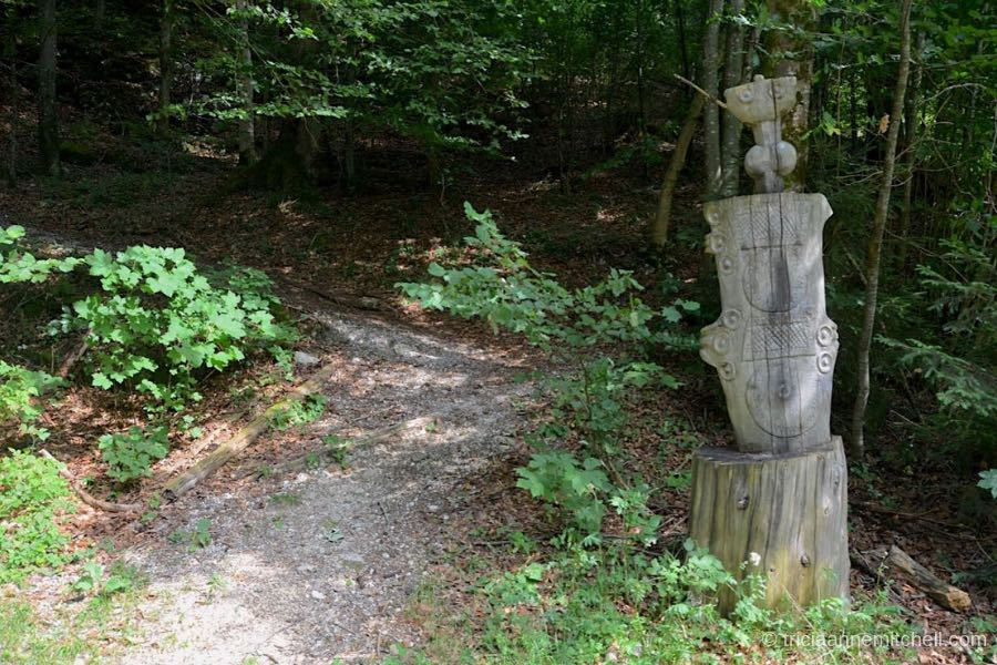 A crushed gravel path leads up a forested hill, past a tree stump that has been carved to look like an ancient Roman dagger.