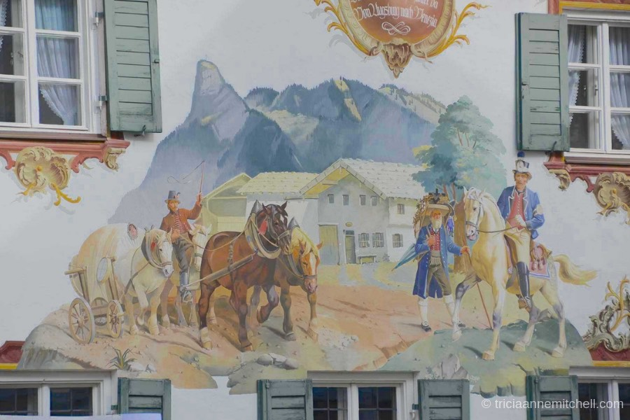 Detail of a mural in Oberammergau, Germany: Horses pull a cart, alongside a merchant carrying wooden objects on his back for sale. A mountain and Bavarian-style home are visible in the background.