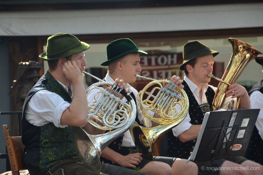 Three men play brass instruments, including French horns, at a festival in Oberammergau, Germany. The men are wearing green Bavarian hats, and traditional vests.