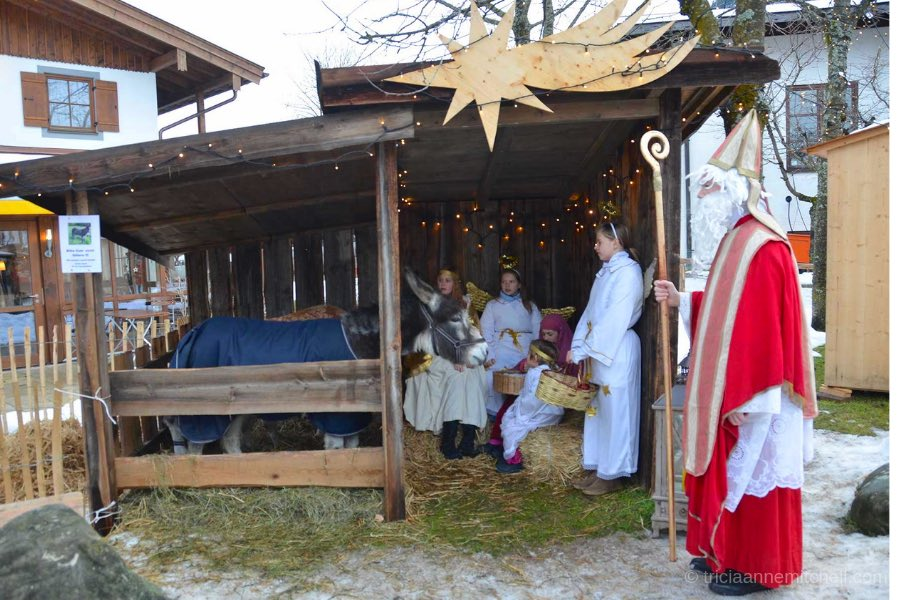 A donkey, girls dressed as angels, and an adult dressed in a red robe of Saint Nicholas stand inside a wooden shed in Oberammergau, Germany. Straw and snow are visible on the ground.