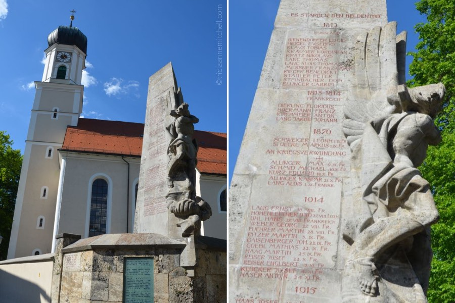 A close-up of Oberammergau's war memorial. It is grey, and the names of soldiers are engraved in red.