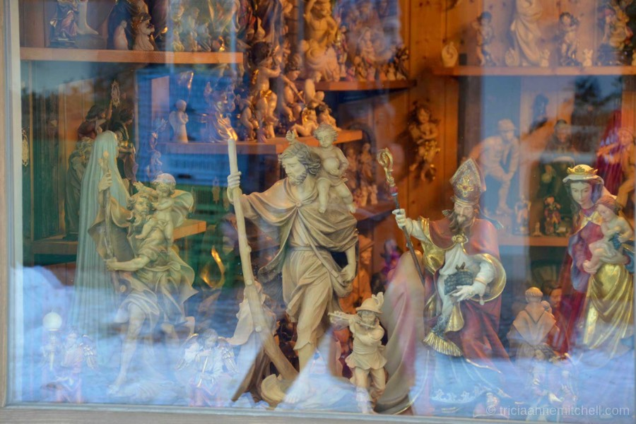 A variety of woodcarvings depicting people and religious saints are visible, viewed through a shopkeeper's window in Oberammergau, Germany.