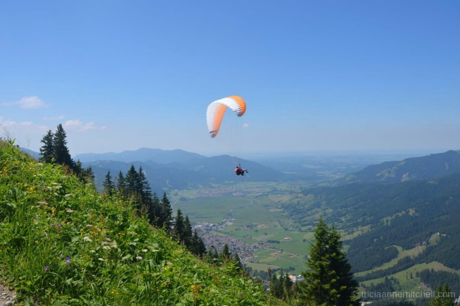 A paraglider with an orange and white parachute flies over the town of Oberammergau, Germany. A steep green hillside carpeted in grass and flowers frames one side. On the other side, you can see the Aufacker Mountain.