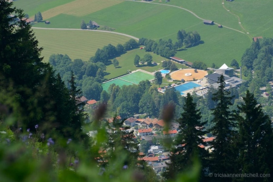 Oberammergau's WellenBerg swimming pools are visible from the top of the Laber. Surrounding them you can see orange rooftops, and green fields.