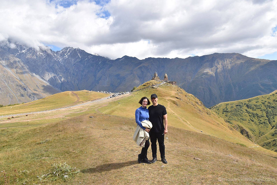 A man and a woman dressed in hiking attire stand in front of the Gergeti Trinity Church in Kazbegi / Stepantsminda, Georgia.