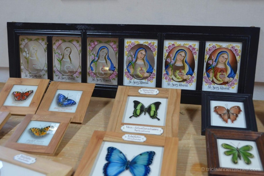 Reverse glass paintings depicting a saint and butterflies for sale at the Pilatushaus workshop in Oberammergau, Germany.