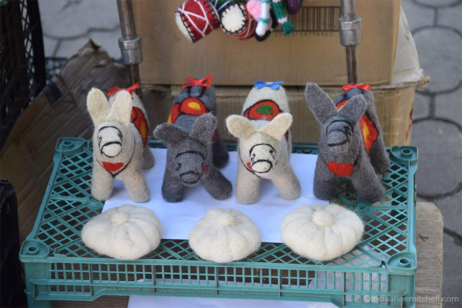 Four woolen donkeys, and three Georgian dumpling toys are displayed at an outdoor market in the town of Sighnaghi.