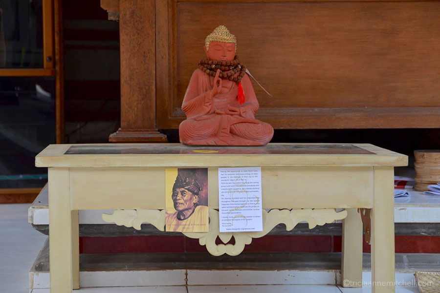 A red Buddha statue sits on a low table inside the courtyard of Ketut Liyer's home in Ubud, Bali. A small photograph of Ketut hangs on the table.