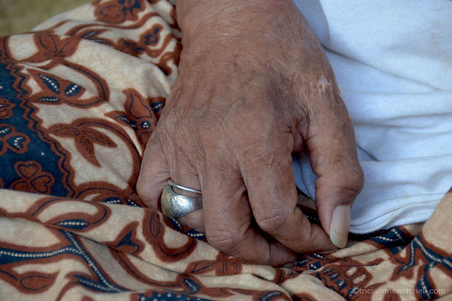 A man's hand rests on his lap.