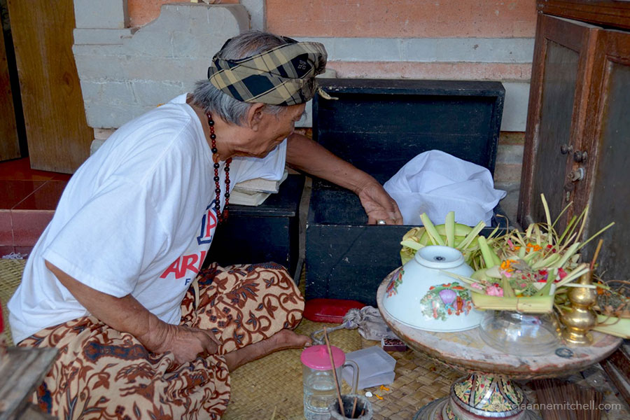 Ketut Liyer searches for a bell inside a wooden chest at his home in Ubud, Bali.