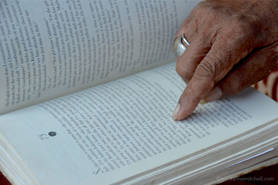 Ketut Liyer points to his name on a page inside the book, Eat, Pray, Love.