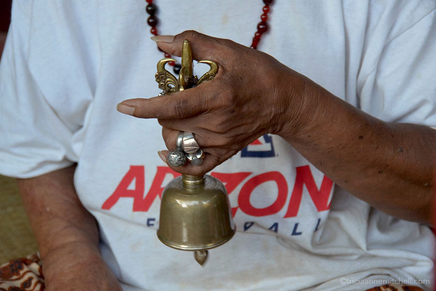A man's hand is visible, ringing a brass bell.