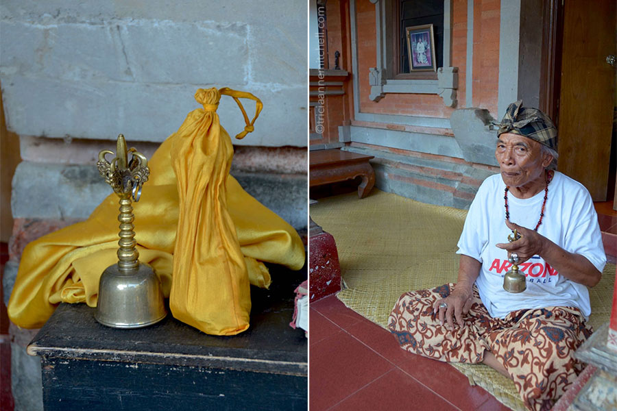 Ketut Liyer rings a brass bell while sitting on the floor on the porch outside his home.