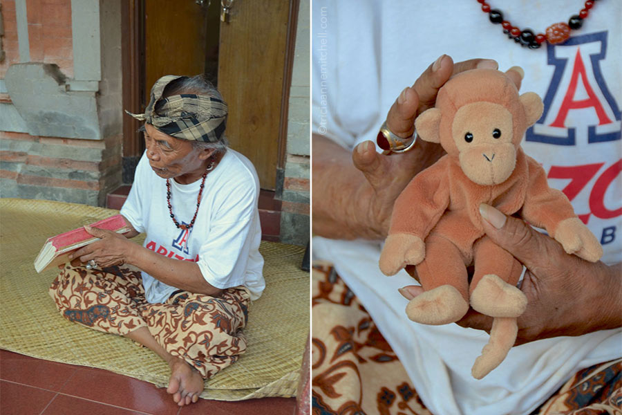 Ketut Liyer holds a signed copy of the book Eat, Pray, Love (left) and a monkey stuffed animal (right).