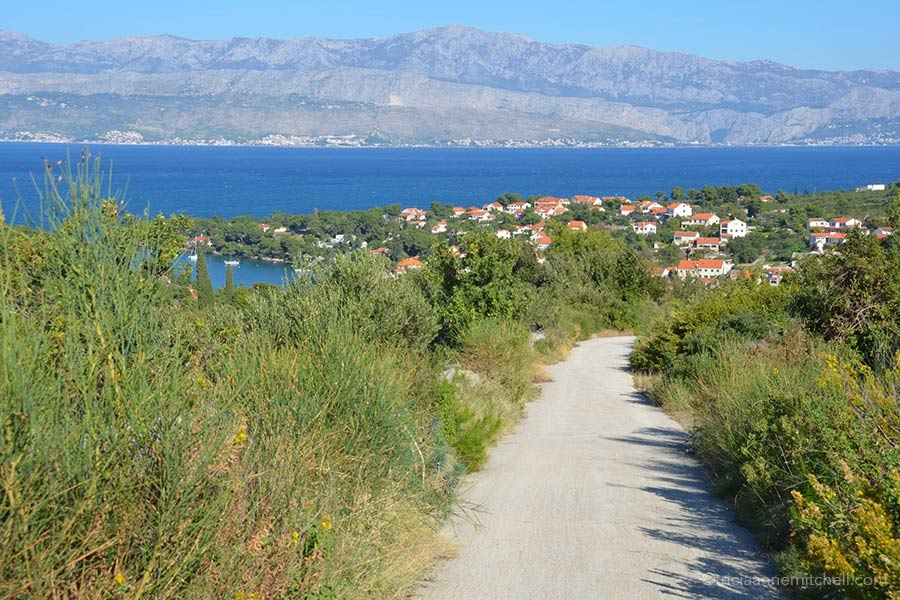 A small road leads towards a village along the coast of the Croatian island of Brač.