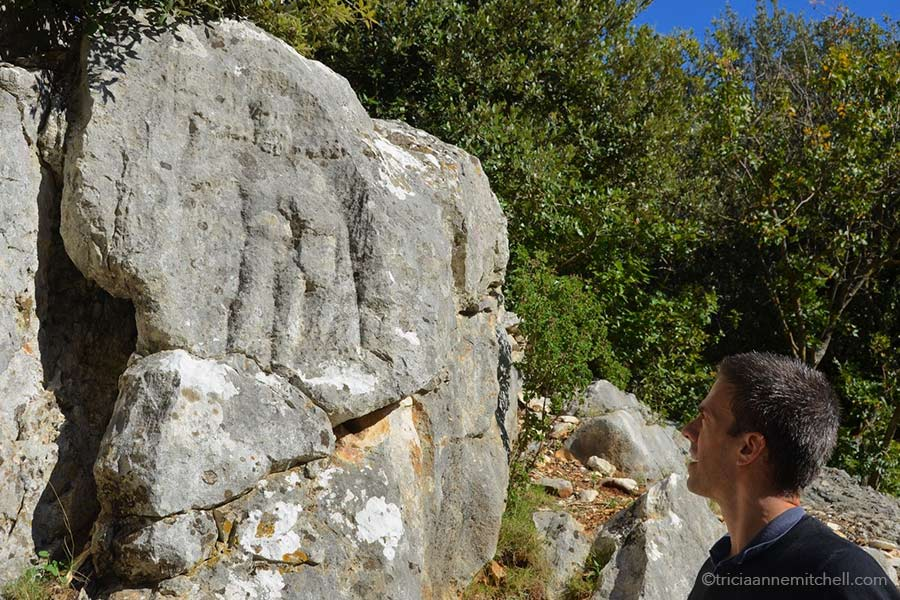 A man looks at the weathered relief depicting Hercules, in an ancient Roman quarry on the Croatian island of Brac.