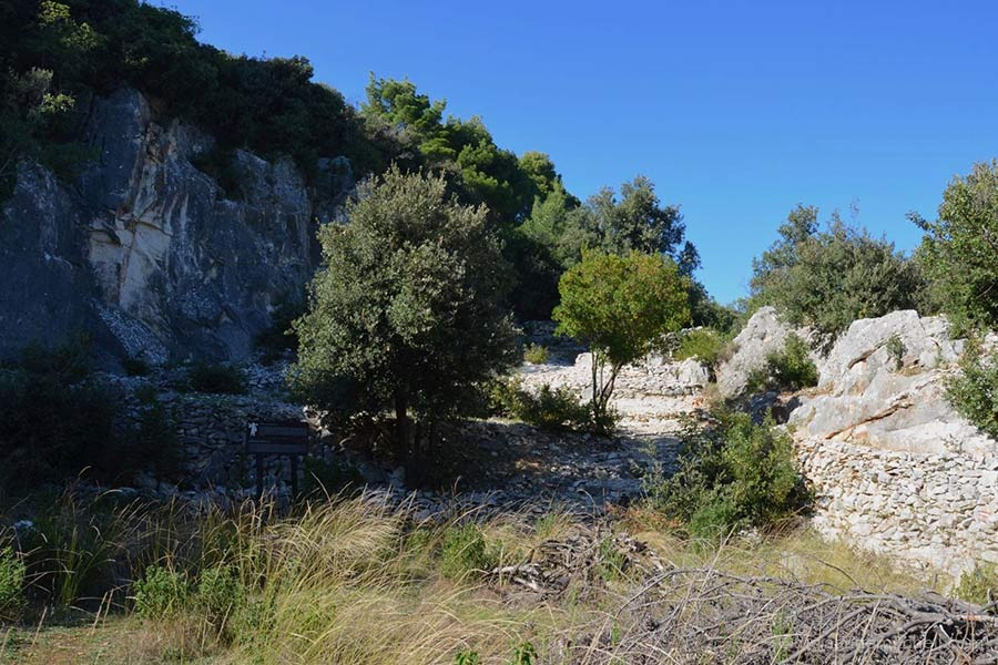 The ancient Roman quarry of Rasohe (on the Croatian island of Brac) has rock walls, trees and shrubs, and a weathered relief of Hercules.
