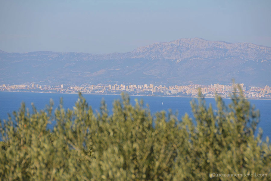 Looking at the city of Split from the neighboring island of Brač. A city skyline, mountains, and sea are visible.