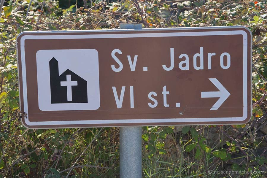 "A sign showing the direction to the Sv. Jadro Church ruins on the Croatian island of Brac. It says ""Sv. Jadro VI st."""