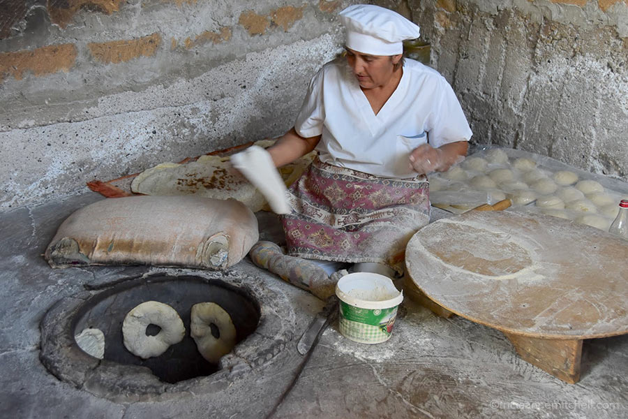 A woman places lavash dough in the oven in the Armenian countryside.