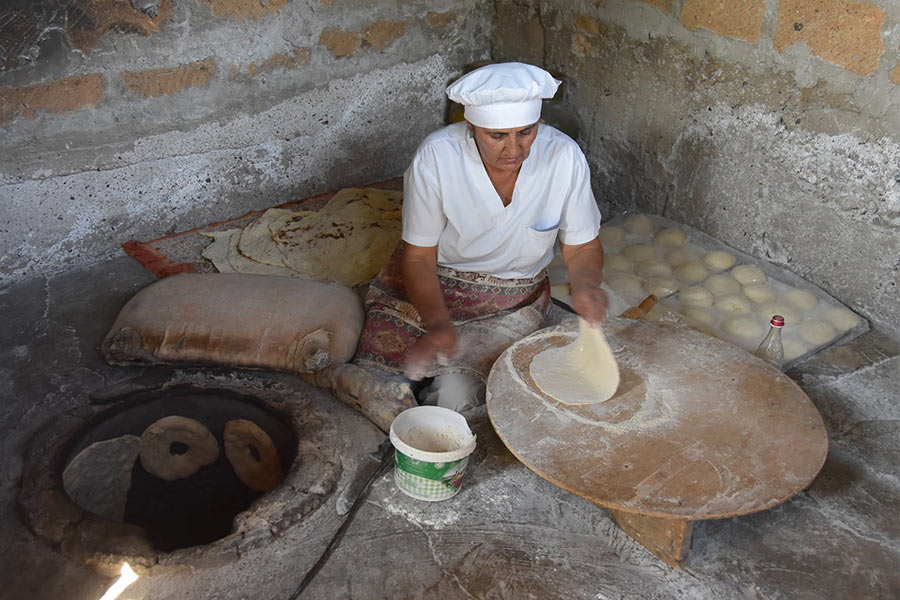 A woman rolls out lavash dough in the Armenian countryside.