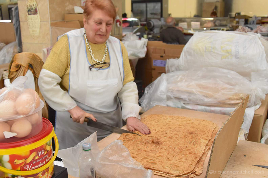 A woman cuts sheets of Armenian lavash into smaller pieces, using a knife. She is at a food market in Yerevan.