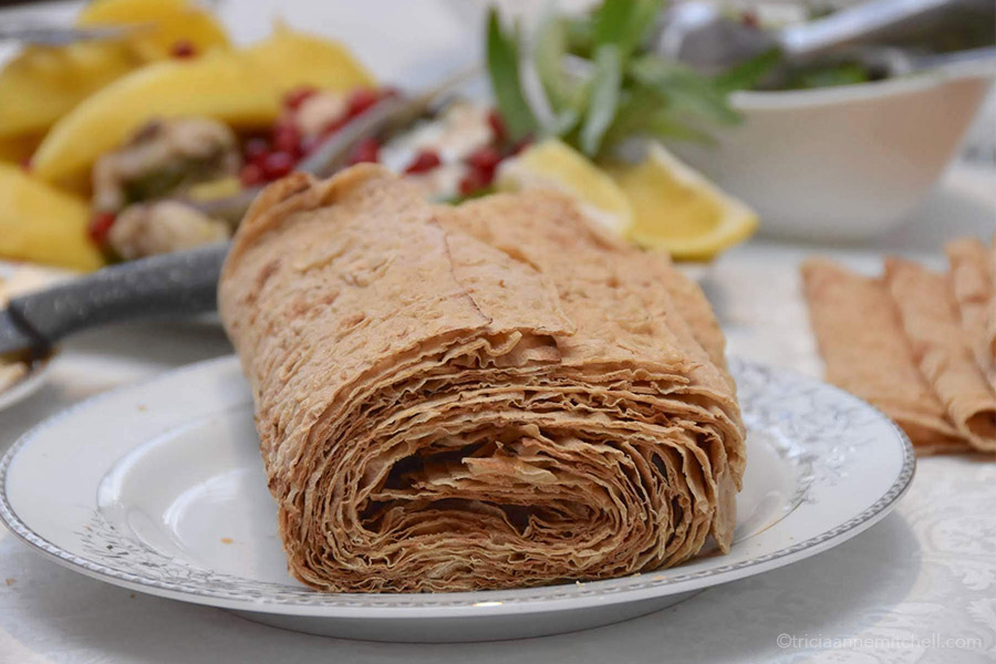 Sheets of lavash, rolled into a tube-like shape on a dining table.