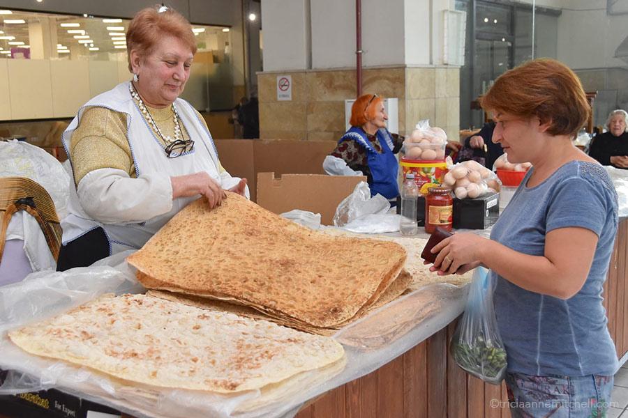 A vendors counts sheets of lavash at a Yerevan fresh-food market.