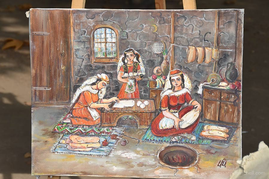 A painting at the Vernissage open-air market depicts women in traditional dress baking lavash.