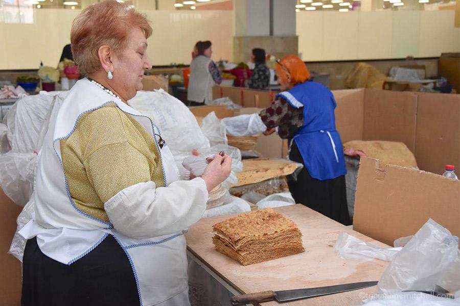 A vendor stacks sheets of lavash at a Yerevan fresh-food market.