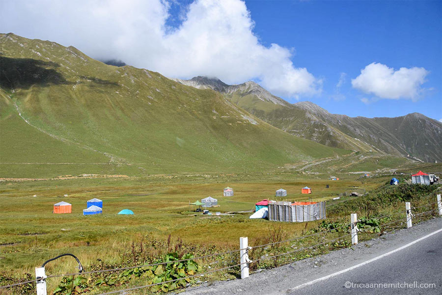 About 7 yurts (ranging in color from blue to orange) dot green mountainous slopes alongside the Georgian Military Highway.