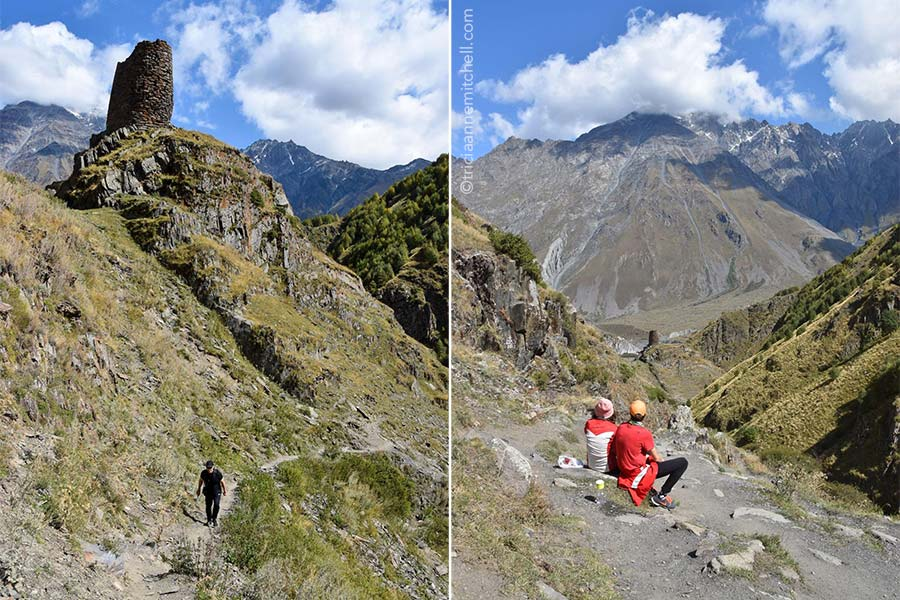 Left: A man dressed in black hikes up a mountain trail in Caucasus Mountains. Right: A couple sitting on a bench pauses to look at the steep mountain slopes that surround them.