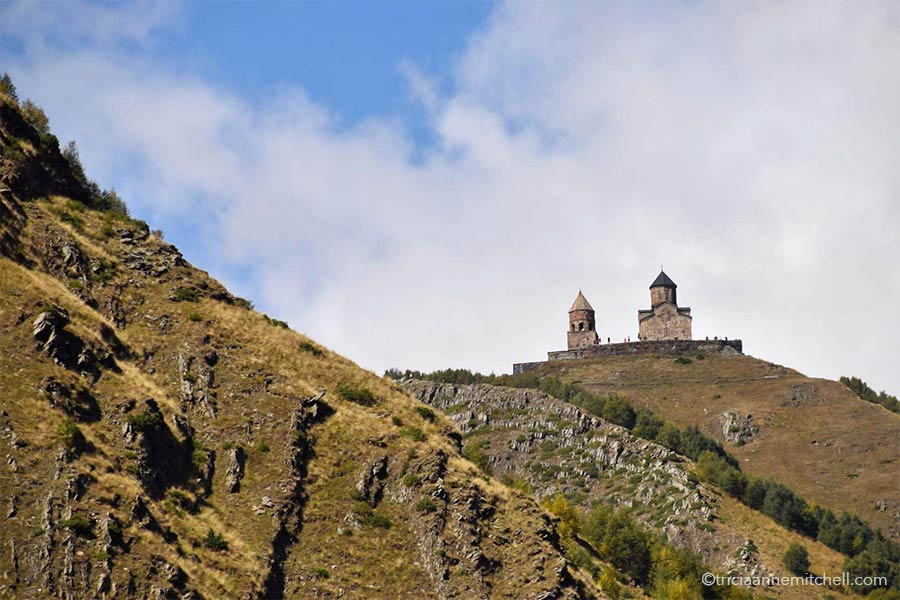 The two towers of the Gergeti Trinity Church in Kazbegi, Georgia are visible. The sky is blue, with clouds, and the mountain slopes are yellowish-brown, with hints of green.
