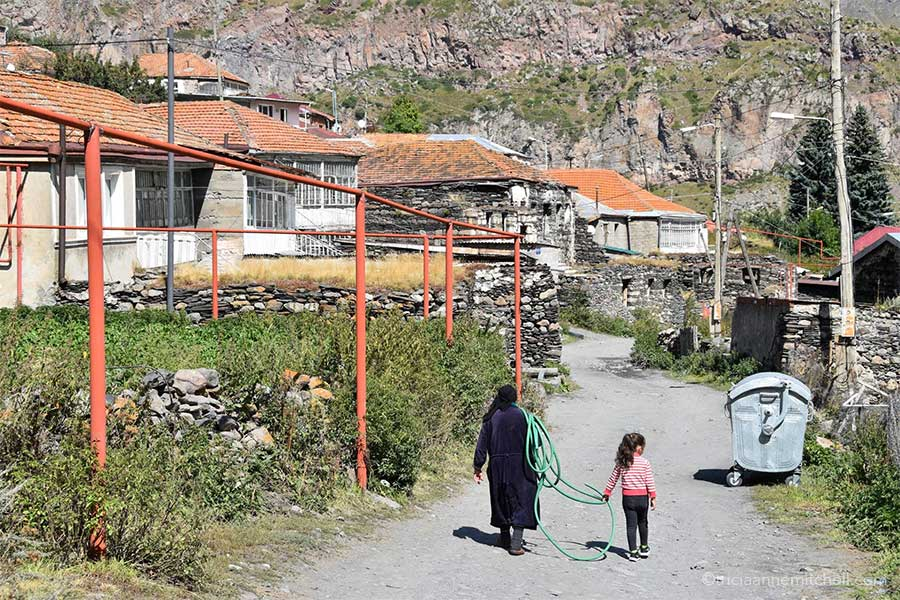An older woman dressed in black carries a green hose with the help of a young girl. They are walking in a Georgian village with stone houses.