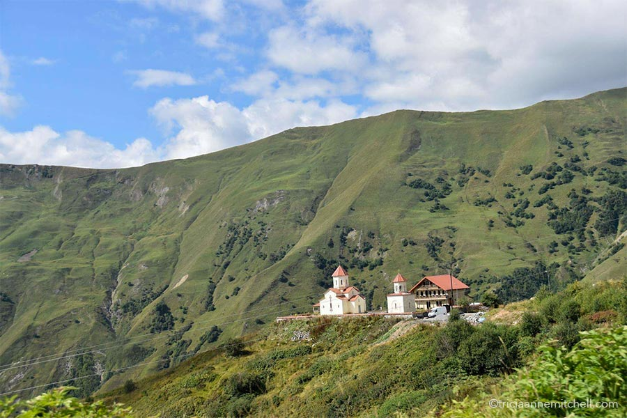 Two churches and a chalet-style house rest on a plateau among mountainous landscape near Gudauri Ski Resort in the Republic of Georgia.