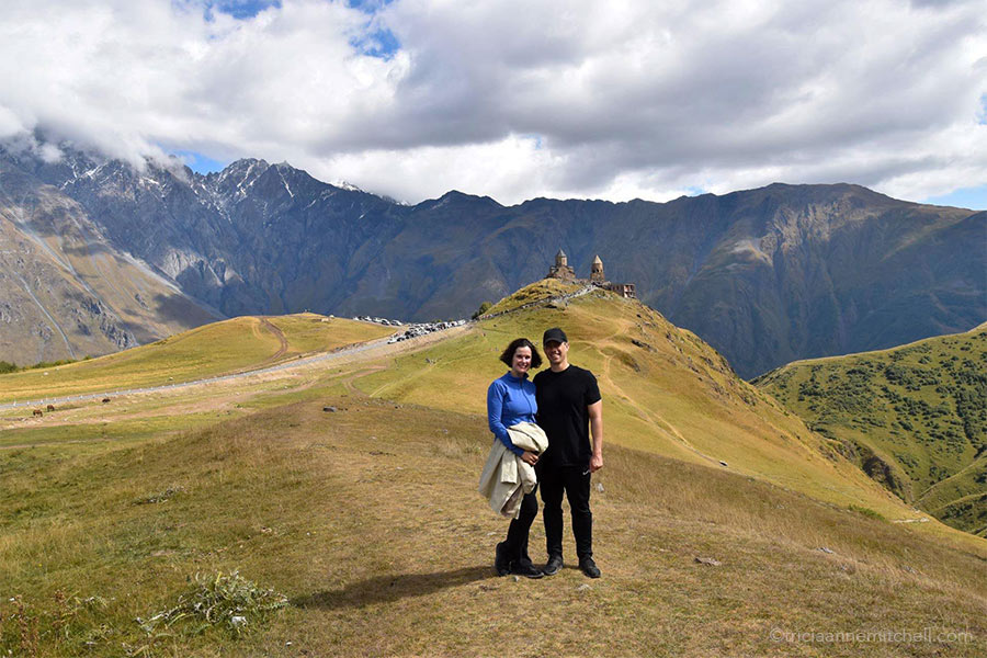 A woman and man stand on the yellowish-green slopes of the Caucasus Mountains in Georgia. The Gergeti Trinity Church (near Kazbegi) is visible in the background.
