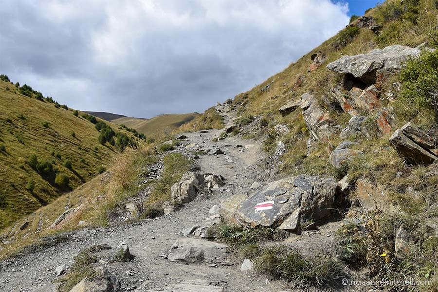 A white and red trail rectangular symbol painted on a rock indicates the correct trail leading to the Gergeti Church near Kazbegi, Georgia.