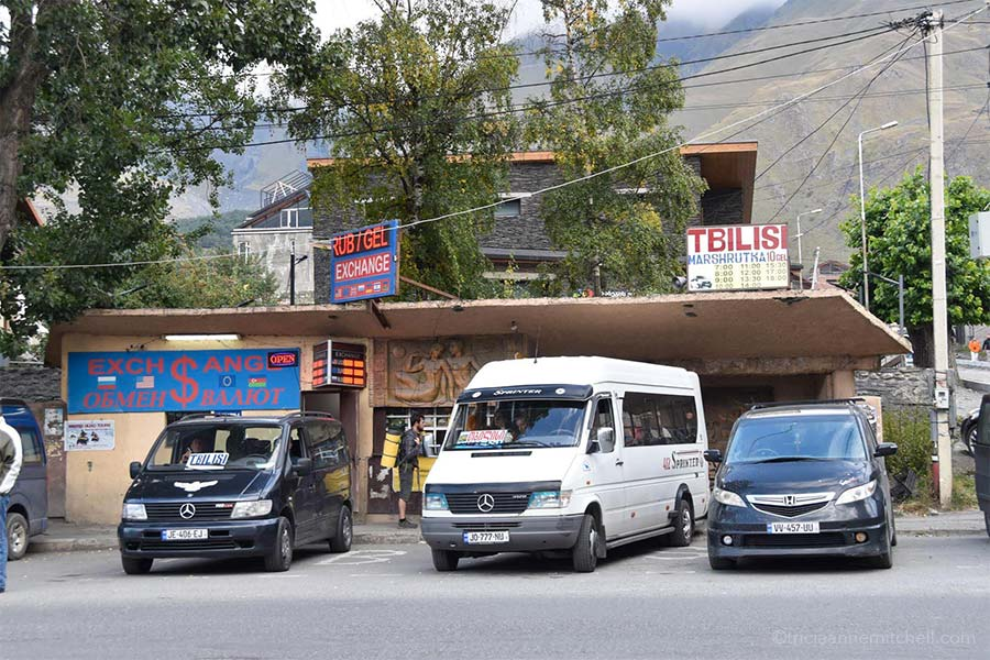 "Three minivans are parked by Kazbegi's taxi stand / marshrutka meeting point. The sign on the left indicates money exchange and says ""RUB GEL Exchange."" Another sign on the right shows the Tbilisi marshrutka schedule. It reads: ""Tbilisi Marshrutka, 10 Gel. 7:00, 8:00, 9:00, 10:00, 11:00. 12:00, 13:00, 14:00, 15:00, 17:00, 18:00."""