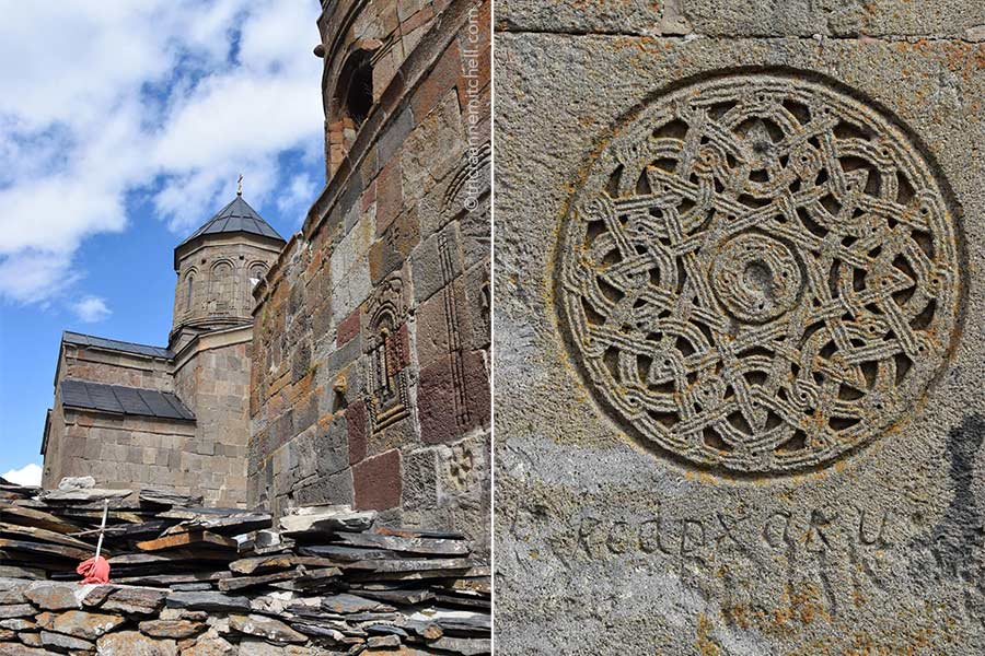 Left: The tower and pinkish-beige wall of the Gergeti Trinity Church near Kazbegi, Georgia. Right: On a wall, an intricate circular symbol is carved. There is centuries-old graffiti below it.