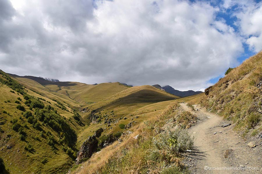 The dirt trail leading to the Gergeti Trinity Church in Kazbegi Georgia. The surrounding hillsides are covered with a yellowish-green grass, and the sky is mostly covered in clouds.