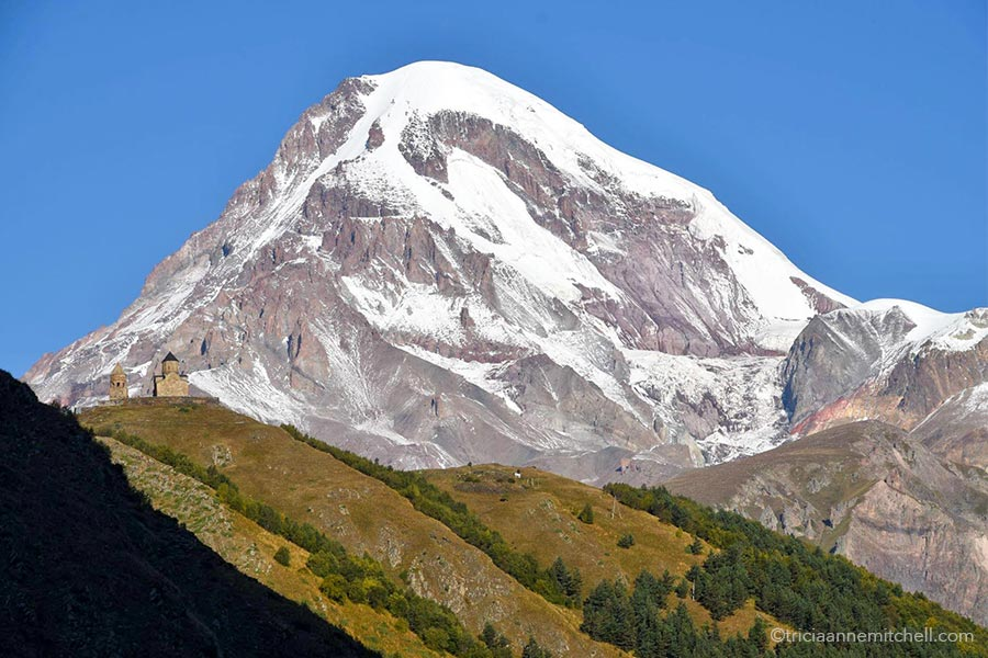 A snowy Mt. Kazbek towers over the beige-colored towers of the Gergeti Trinity Church in Georgia.